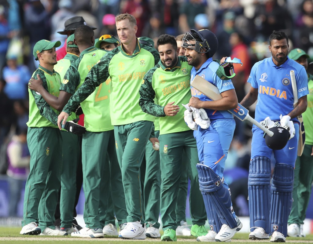 South Africa's Tabraiz Shamsi, third right, congratulates India's Rohit Sharma, second right, on their their win in the Cricket World Cup match betwee...