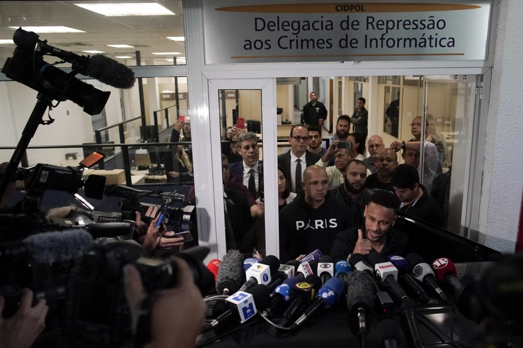 Brazilian soccer player Neymar gives a thumbs up after speaking to journalists as he leaves a police station where he spoke to police in Rio de Janeir...