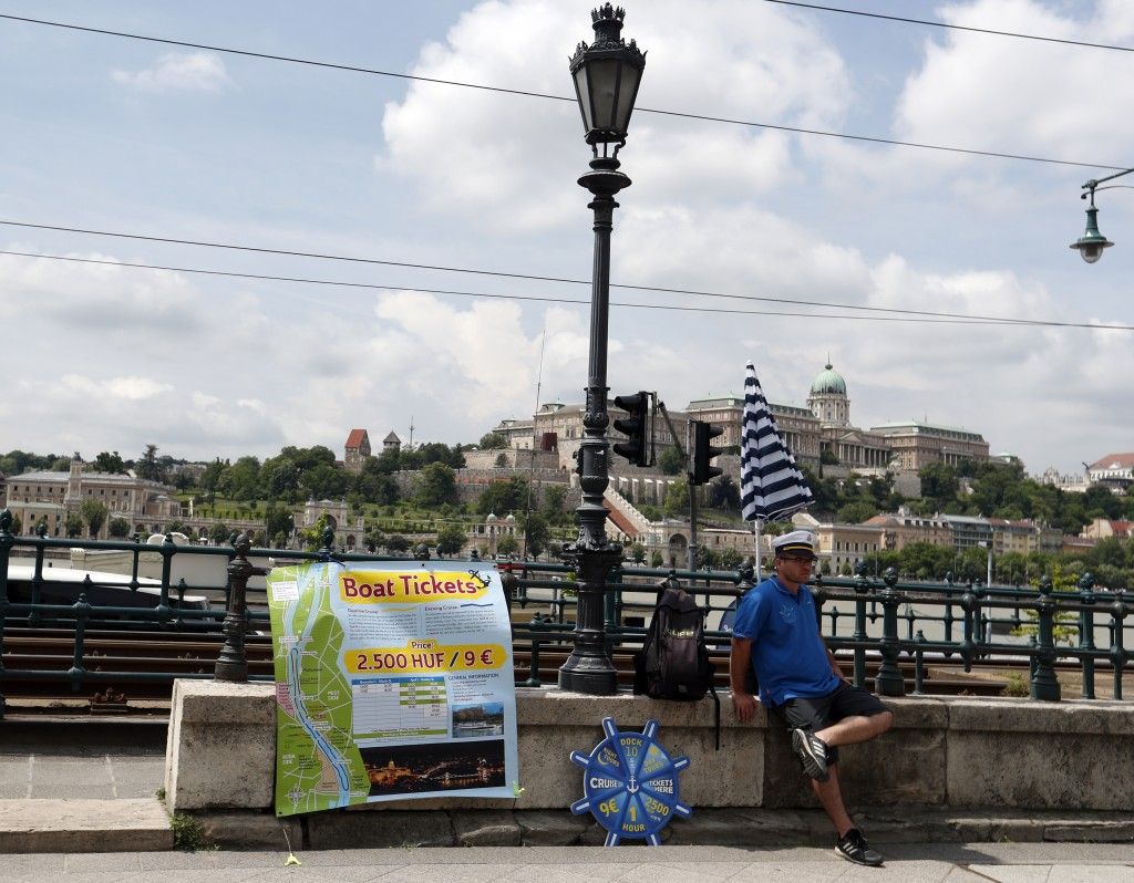 In this photo taken on Wednesday, June 5, 2019, a man sells tour boat tickets near the Danube River in Budapest, Hungary. A tourism boom in the Hungar...