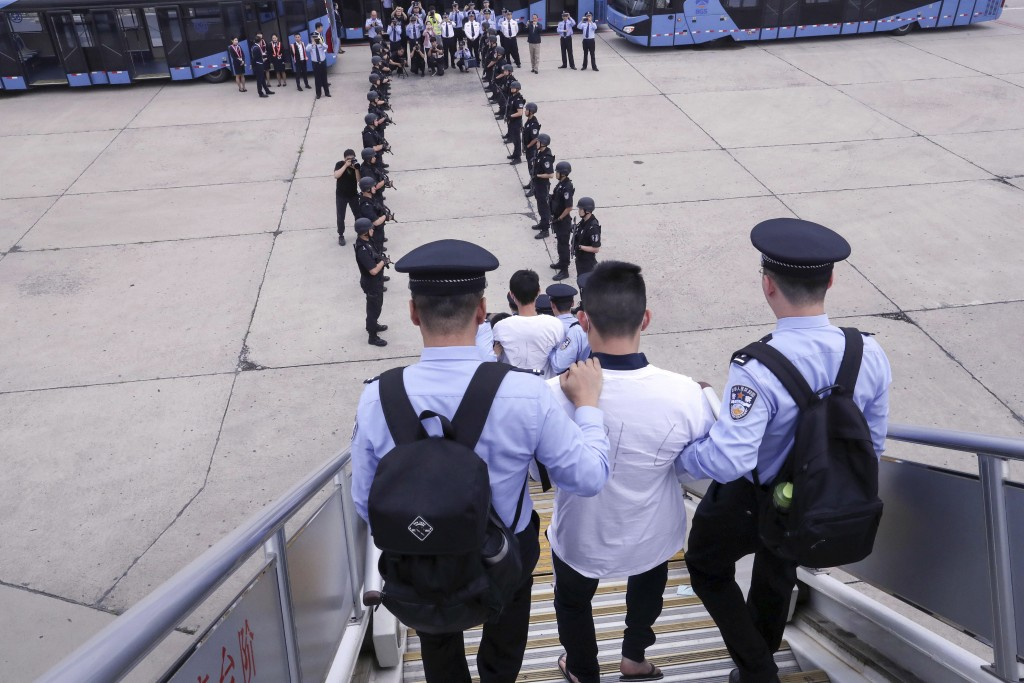 In this photo released by China's Xinhua News Agency, police escort criminal suspects as they get off a plane at Beijing Capital International Airport...