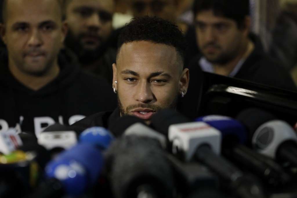 Brazilian soccer player Neymar speaks to journalists as he leaves a police station where he spoke to police in Rio de Janeiro, Brazil, Thursday, June ...