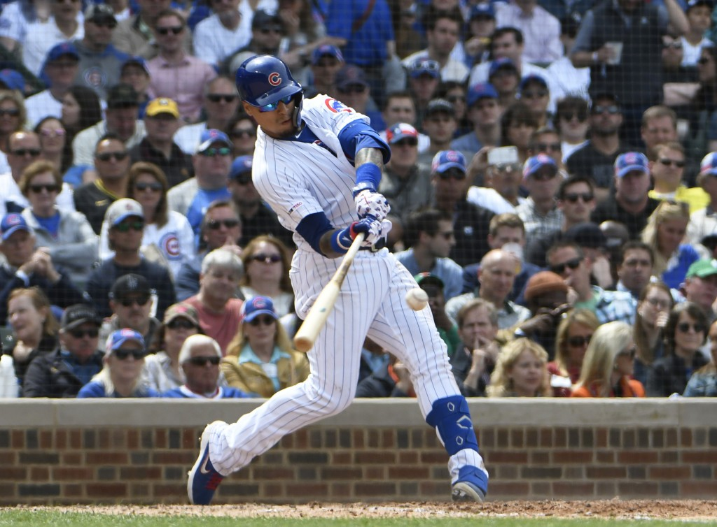 Chicago Cubs' Javier Baez (9) hits a one run single against the Colorado Rockies during the sixth inning of a baseball game, Thursday, June, 6, 2019, ...