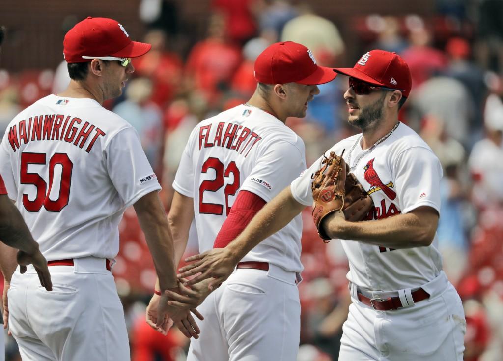 St. Louis Cardinals' Paul DeJong, right, celebrates with teammates Adam Wainwright (50) and Jack Flaherty (22) after a 3-1 victory over the Cincinnati...