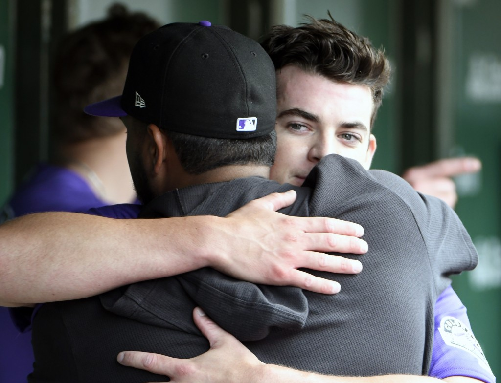 Colorado Rockies starting pitcher Peter Lambert, back, gets hug from Colorado Rockies starting pitcher German Marquez (48), front, in the dugout after...