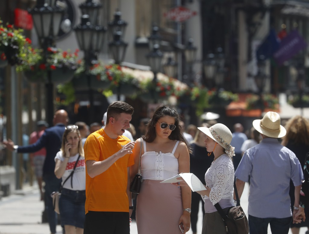 In this photo taken on Wednesday, June 5, 2019, tourists talk with a woman offering tourism services on Vaci Street in downtown Budapest, Hungary. A t...