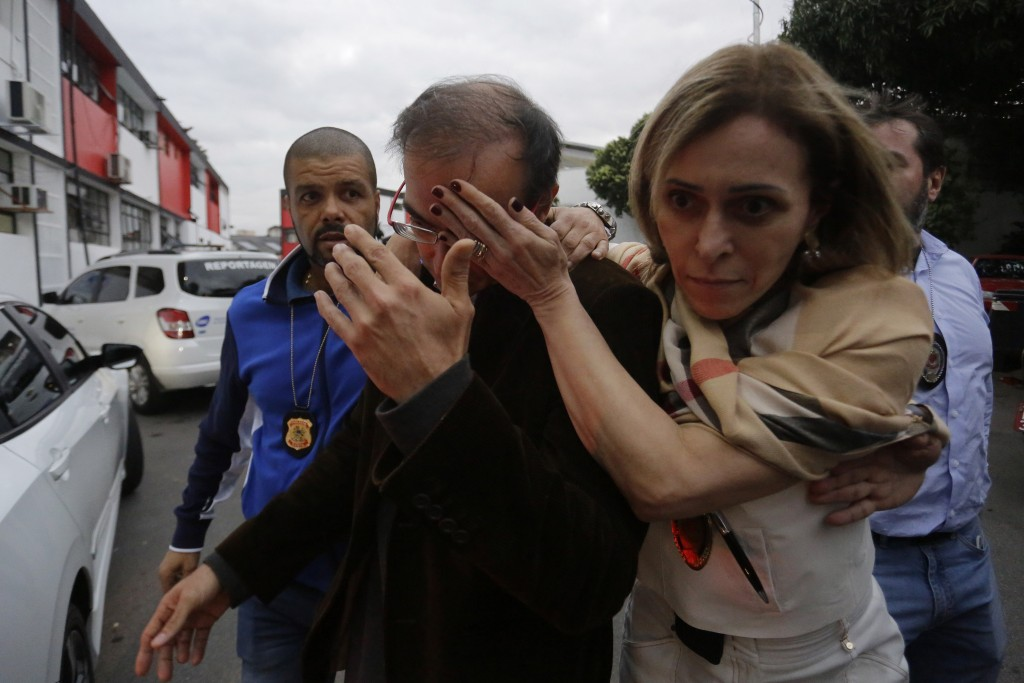 A police officer, right, covers the face of Dr. Luiz Eduardo Rossi Campedelli as he leaves a police station after giving a statement about the medical...