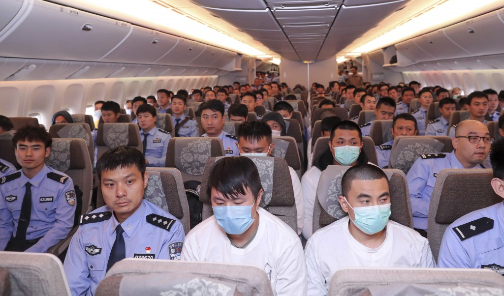 In this photo released by China's Xinhua News Agency, police and criminal suspects sit on a plane at Beijing Capital International Airport in Beijing,...