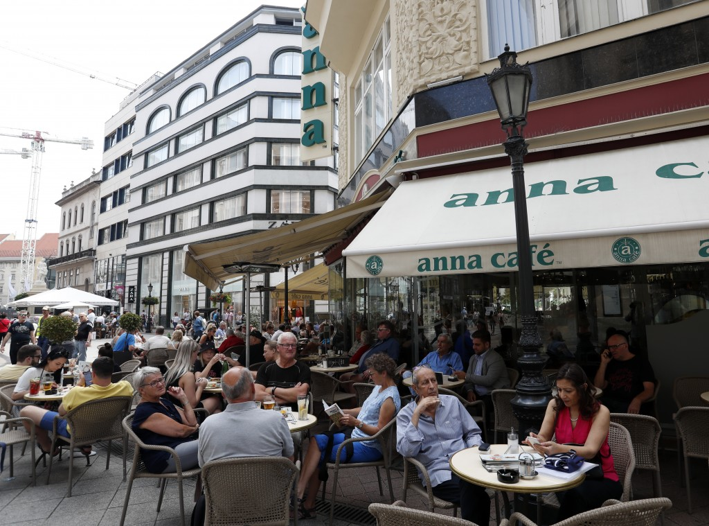 In this photo taken on Wednesday, June 5, 2019, people sit at a cafe on Vaci Street in downtown Budapest. A tourism boom in the Hungarian capital has ...