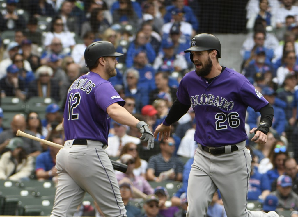 Colorado Rockies' David Dahl (26) is greeted by Mark Reynolds (12) after scoring against the Chicago Cubs during the fourth inning of a baseball game,...