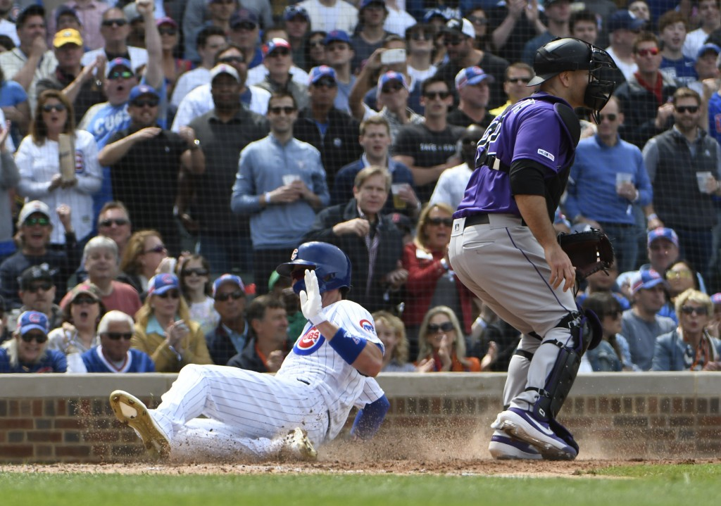 Chicago Cubs' Kris Bryant, left, slides safely into home plate as Colorado Rockies catcher Chris Iannetta (22) waits for a throw during the sixth inni