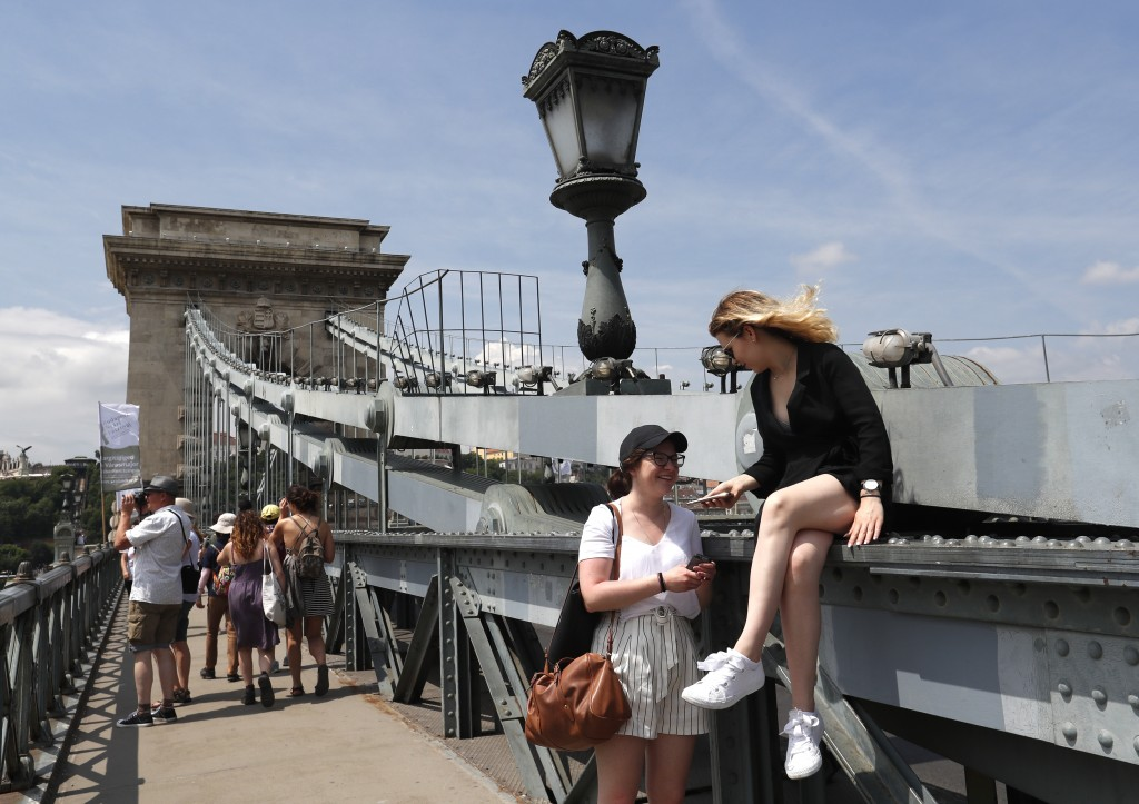 In this photo taken on Wednesday, June 5, 2019, tourists and Hungarians walk on the Chain Bridge over the Danube River in Budapest. A tourism boom in ...