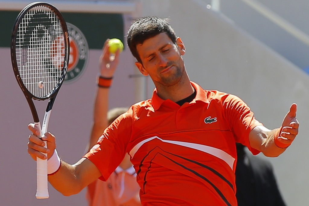 Serbia's Novak Djokovic reacts after missing a shot against Austria's Dominic Thiem in their semifinal match of the French Open tennis tournament at t