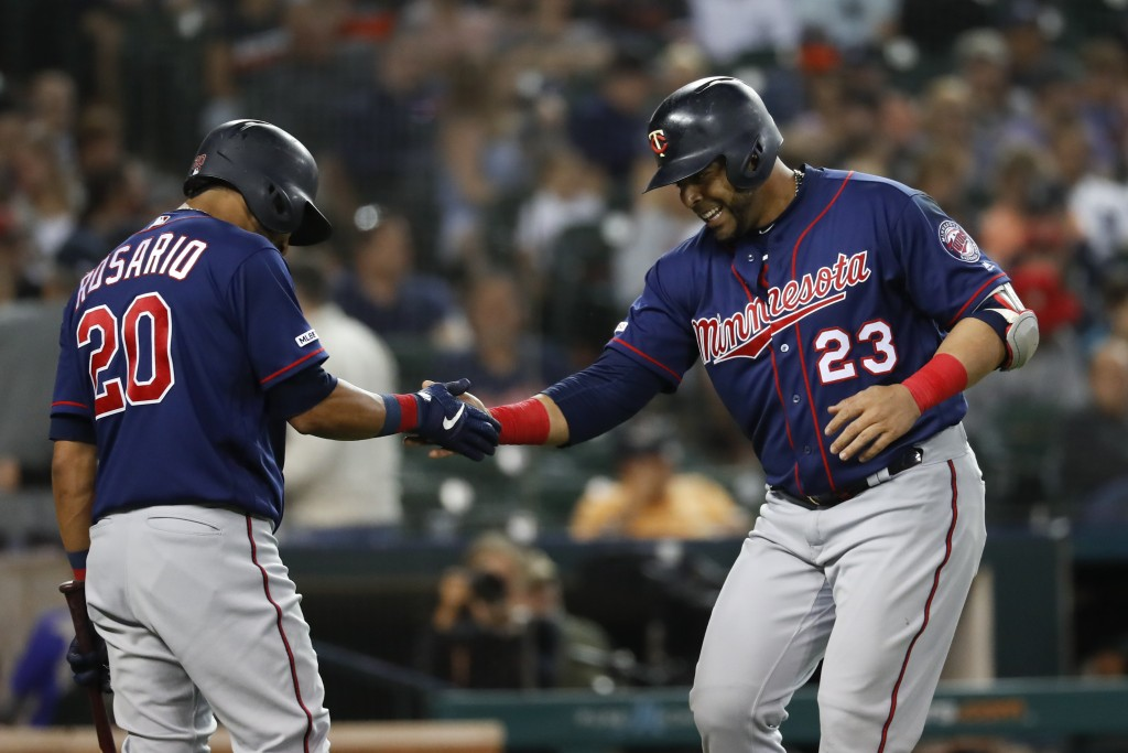 Minnesota Twins' Nelson Cruz (23) celebrates his solo home run with Eddie Rosario (20) during the eighth inning of the team's baseball game against th