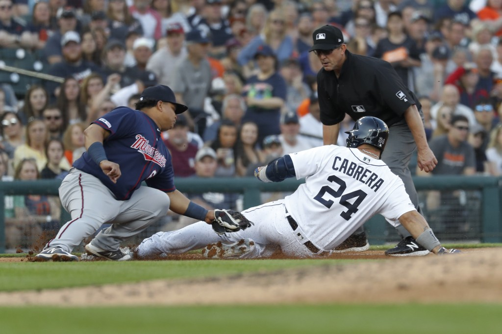 Detroit Tigers' Miguel Cabrera (24) slides safely into third base under the tag of Minnesota Twins' Willians Astudillo (64) in the fourth inning of a