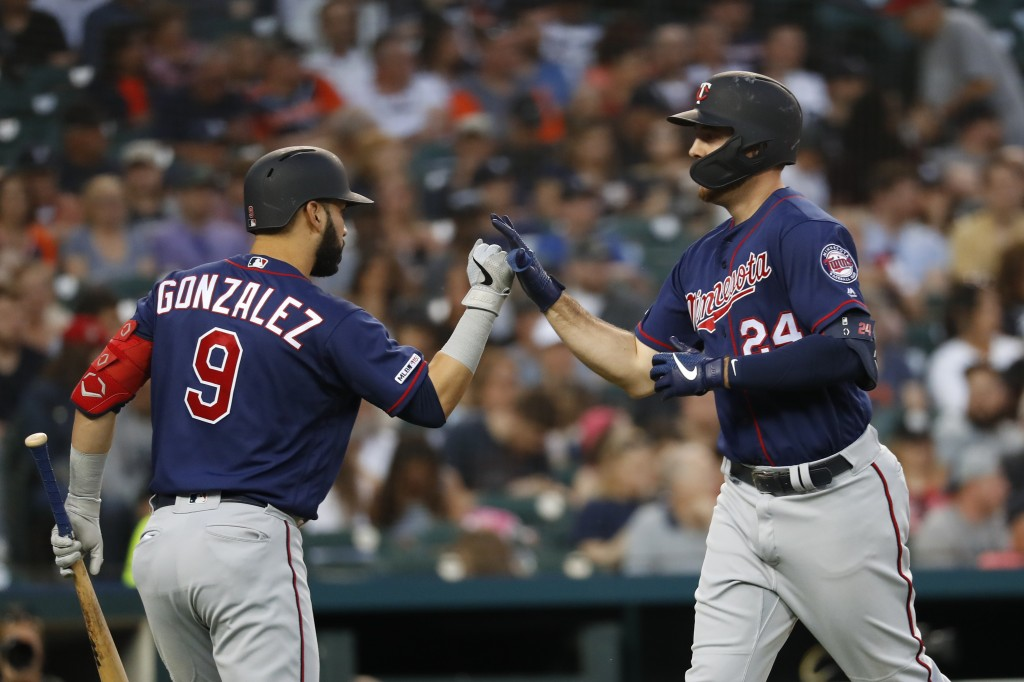 Minnesota Twins' C.J. Cron (24) celebrates his solo home run with Marwin Gonzalez (9) in the sixth inning of a baseball game against the Detroit Tiger