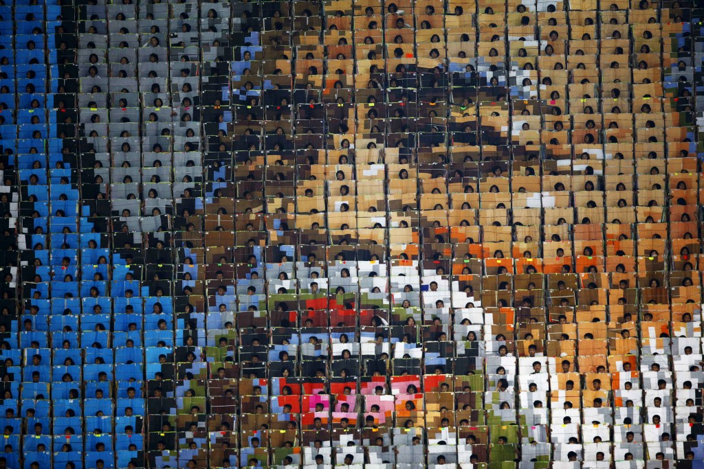 """In this Friday, June 7, 2019, file photo, students hold cards to form pattern of smiling face of an old man during the mass game performance of """"The L"""