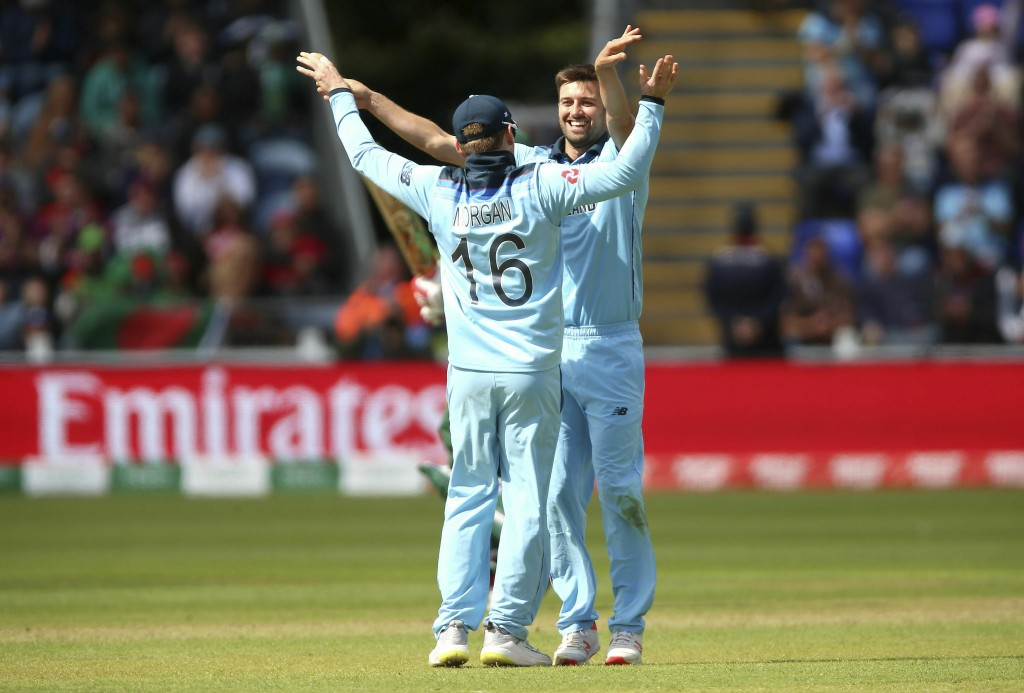 England's Mark Wood, right, celebrates with teammate Eoin Morgan after the catch of Bangladesh's Tamim Iqbal during the ICC Cricket World Cup group st