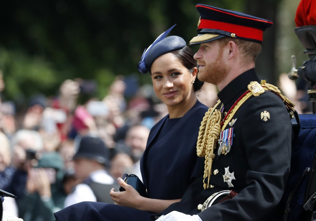 FILE - In this Saturday, June 8, 2019 file photo, Britain's Meghan, the Duchess of Sussex and Prince Harry ride in a carriage to attend the annual Tro...