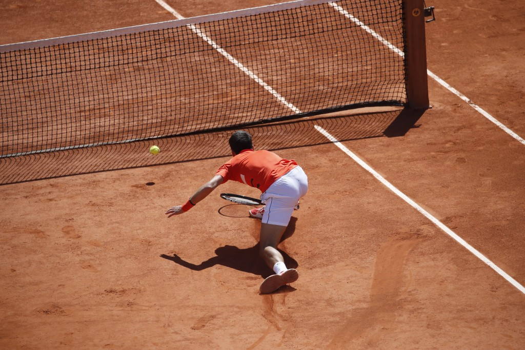 Serbia's Novak Djokovic slides to the net but fails to return a shot by Austria's Dominic Thiem during their semifinal match of the French Open tennis