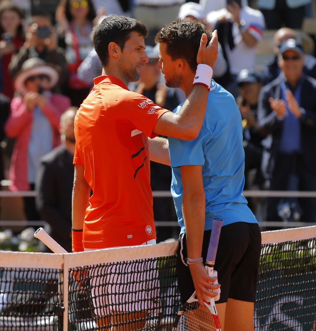 Serbia's Novak Djokovic, left, congratulates Austria's Dominic Thiem with winning his semifinal match of the French Open tennis tournament at the Rola...