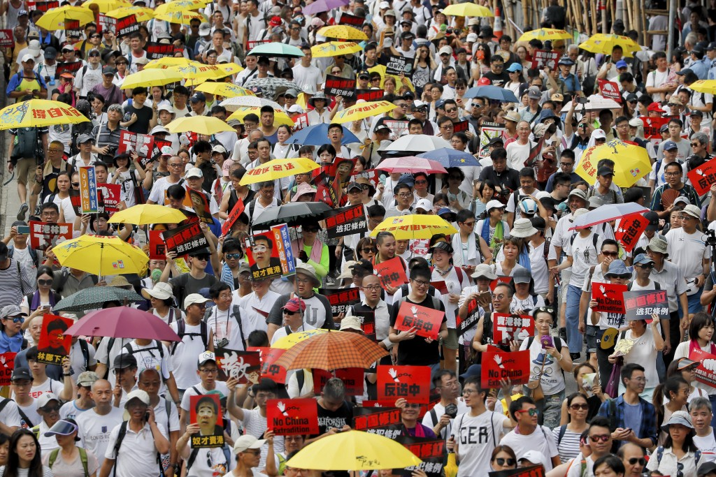 Protesters hold umbrellas and placards march on a street as they take part in a rally against the extradition law in Hong Kong Sunday, June 9, 2019. T...