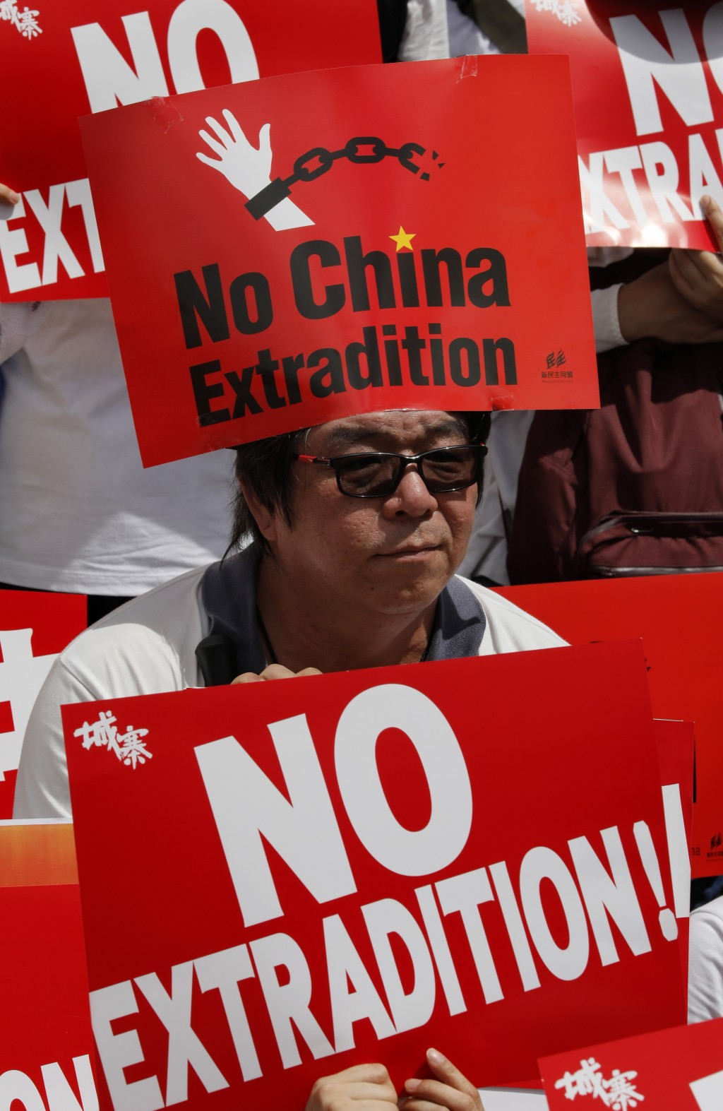 A man raises placards as ten of thousands of protesters march along a downtown street to against the proposed amendments to an extradition law in Hong...