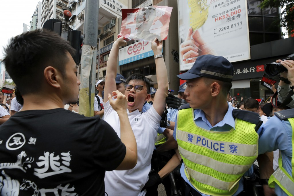 In this June 9, 2019, file photo protester shouts next to policemen as protesters march in a rally against the proposed amendments to extradition law ...