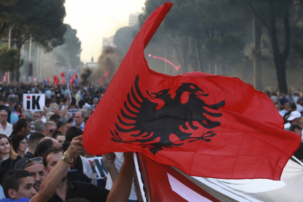 A demonstrator waves the Albanian national flag during an anti-government protest in Tirana, Albania, Saturday, June 8, 2019. Thousands of Albanian op...