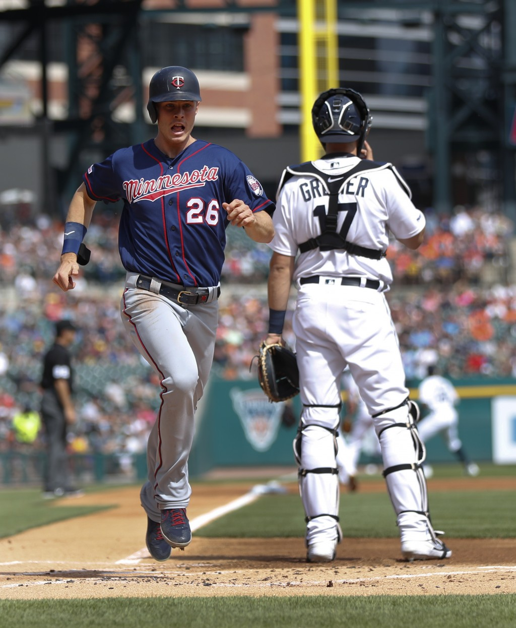 Minnesota Twins' Max Kepler (26) scores against the Detroit Tigers on a Jorge Polanco double in the first inning of a baseball game in Detroit, Saturd
