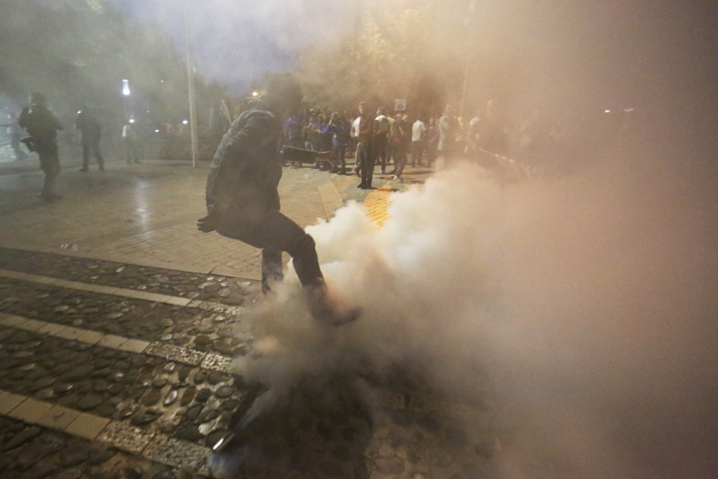 A demonstrator tries to kick away a tear gas canister during an anti-government protest in Tirana, Albania, Saturday, June 8, 2019. Thousands of Alban