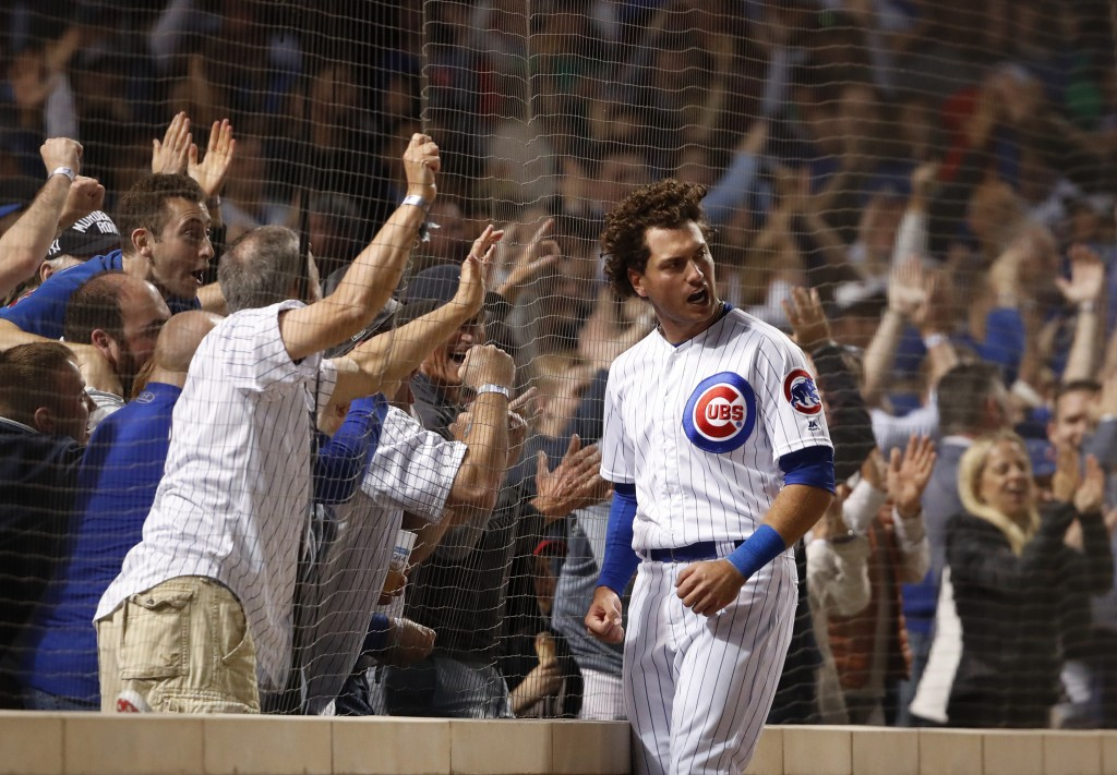 Chicago Cubs' Albert Almora Jr. celebrates against the fence after scoring a run against the St. Louis Cardinals during the sixth inning of a baseball