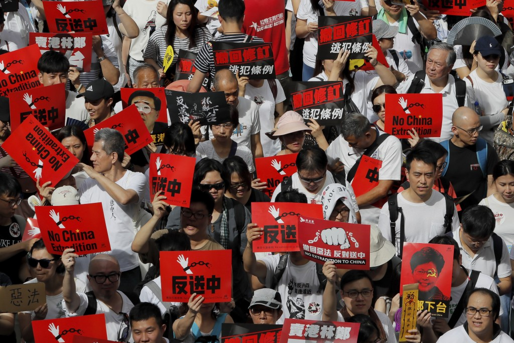 Protesters hold placards march in a rally against the proposed amendments to extradition law in Hong Kong, Sunday, June 9, 2019. The amendments have b...