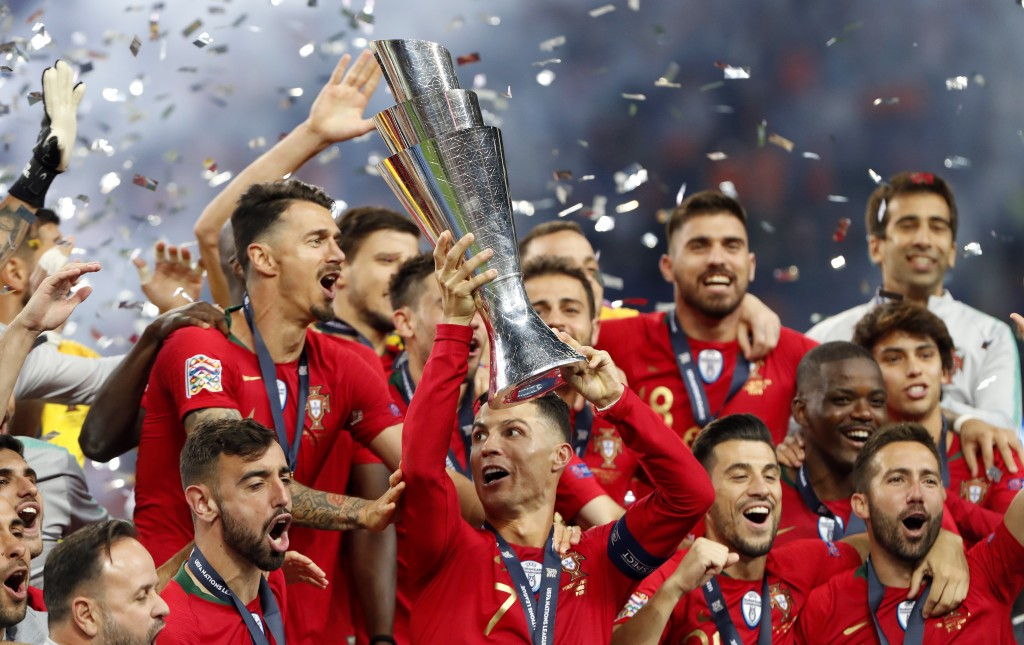 Portugal players celebrate with their trophy after...