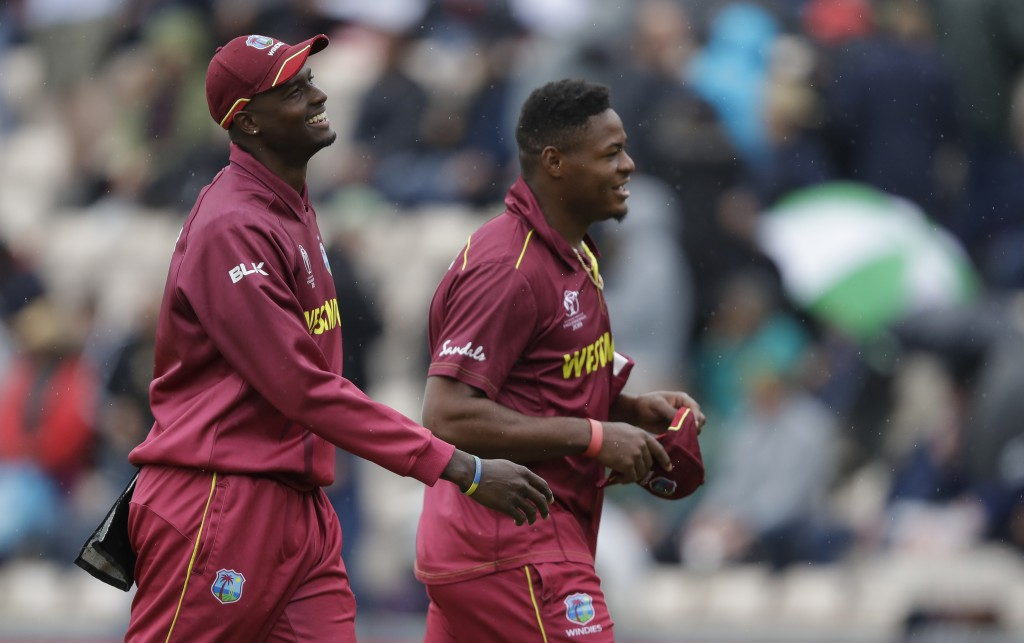 West Indies' captain Jason Holder , left, and West Indies' Oshane Thomas smile as they leave the pitch as rain stops play during the World Cup cricket