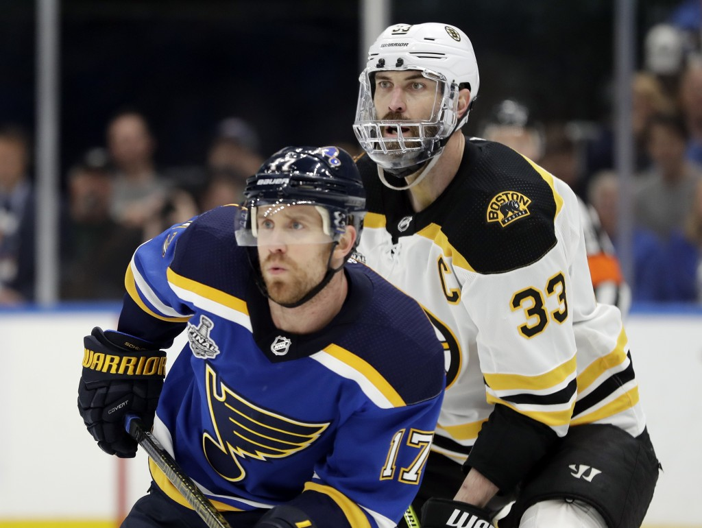 Boston Bruins defenseman Zdeno Chara (33), of Slovakia, wears a mask to protect his injured jaw as he and St. Louis Blues left wing Jaden Schwartz (17