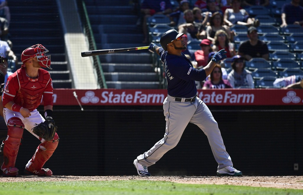 Seattle Mariners' Edwin Encarnacion, right, hits a two-run home run as Los Angeles Angels catcher Jonathan Lucroy watches during the seventh inning of