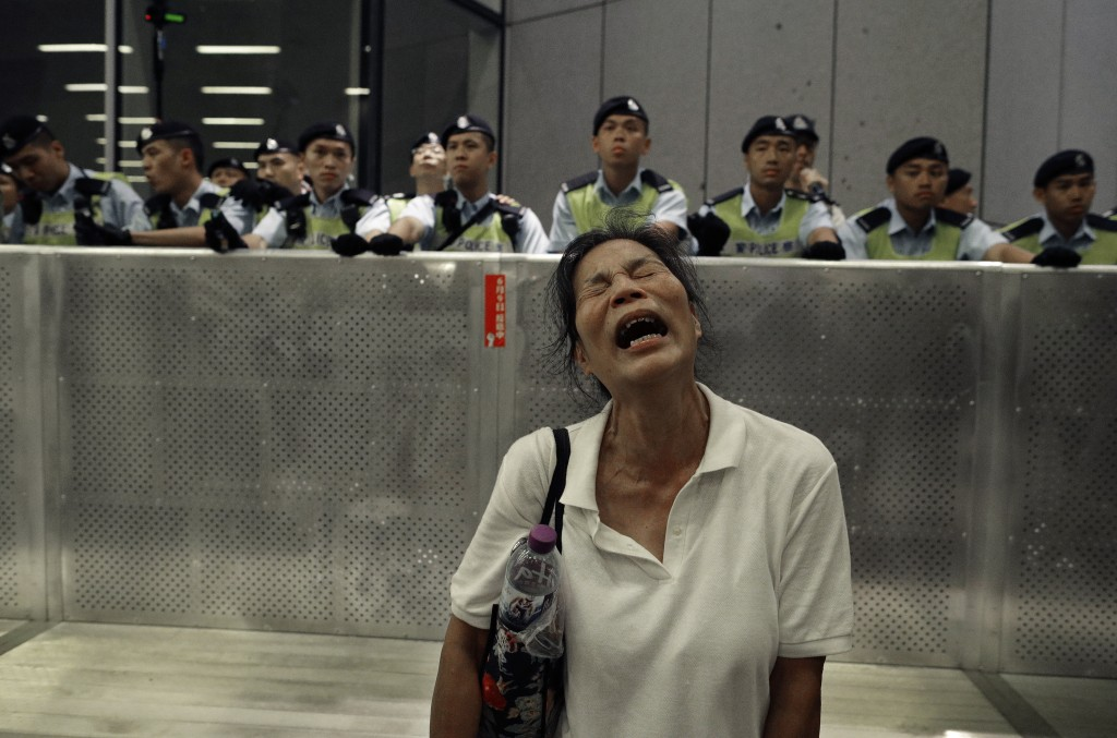 In this Monday, June 10, 2019, file photo, a protester reacts as police officers clash with protesters in a rally against the proposed amendments to t
