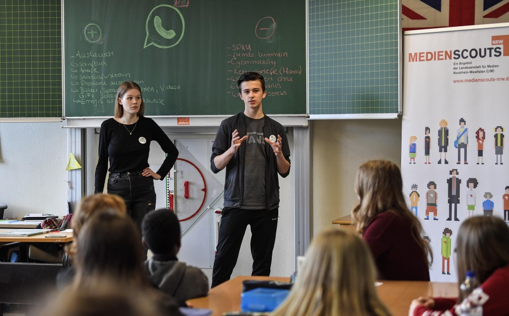 Senior students and media scouts Leon Zielinski, right, and Chantal Hueben teach younger pupils during a lesson in social media and internet at a comp...