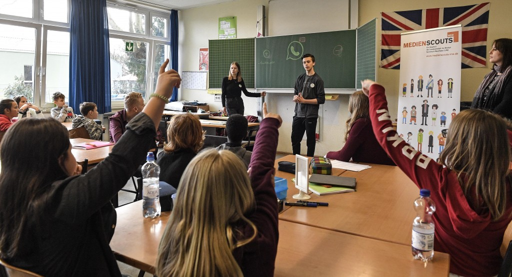 Senior students and media scouts Leon Zielinski and Chantal Hueben, in the background, teach younger pupils during a lesson in social media and intern...