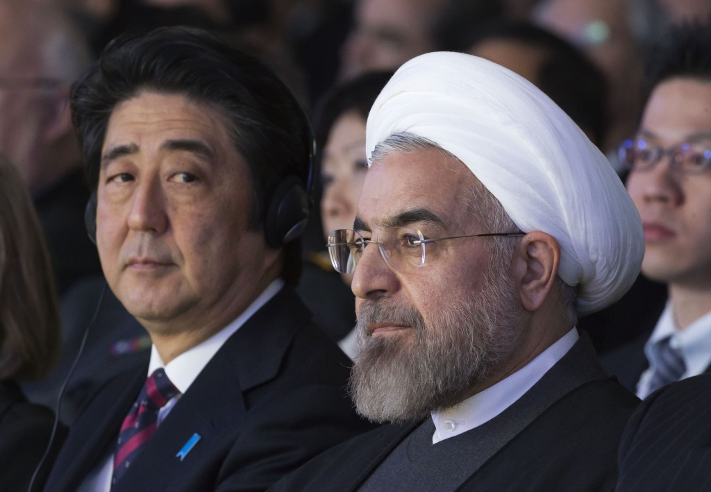 FILE - In this Jan. 22, 2014 file photo, Japanese Prime Minister Shinzo Abe, left, and Iranian President Hassan Rouhani, attend a session of the World...