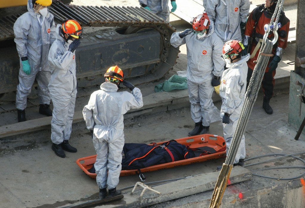 Rescue team members salute next to a recently found victim during the recovery operation at Margaret Bridge, the scene of the fatal boat accident in B...