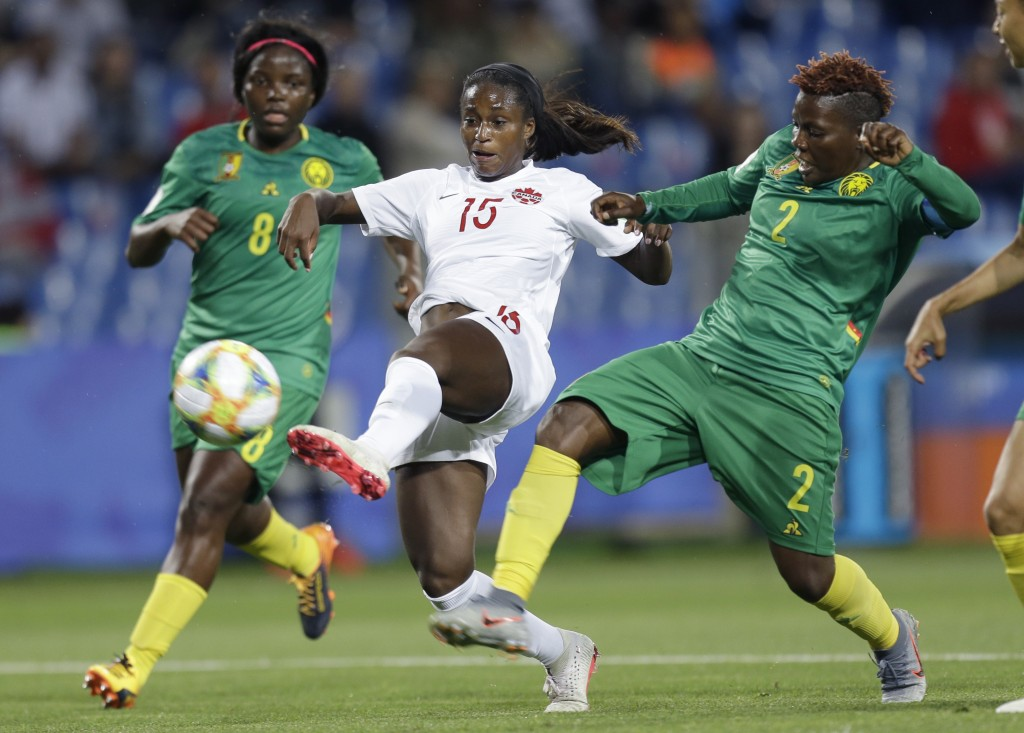 Canada's Nichelle Prince battles for the ball with Cameroon's Christine Manie, right, and Raissa Feudjio, left, during the Women's World Cup Group E s