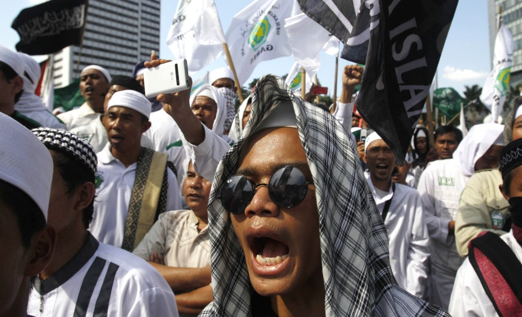 FILE - In this May 3, 2013, file photo, members of the militant Islamic Defenders Front (FPI) shout slogan during a demonstration in Jakarta, Indonesi
