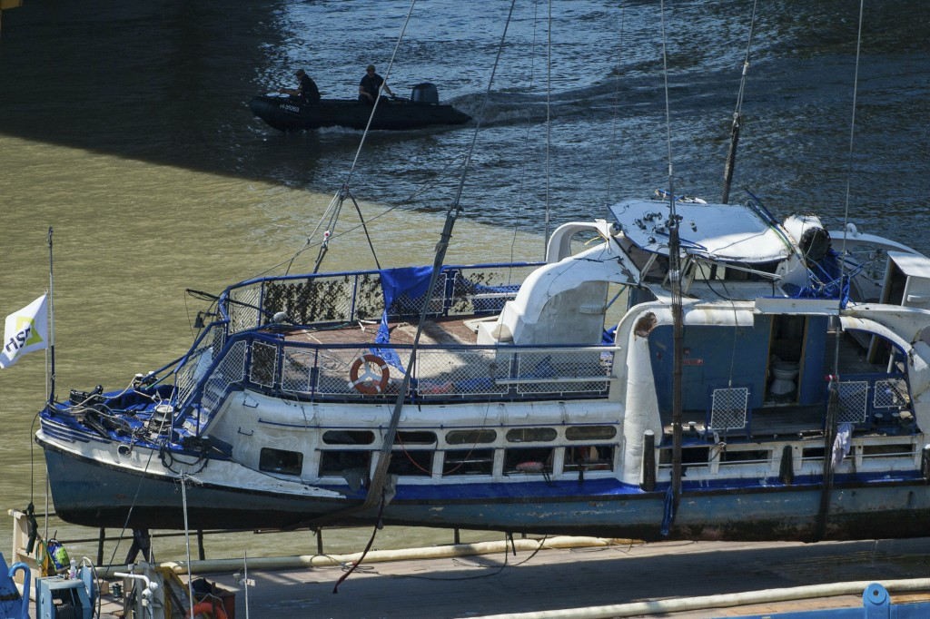 A crane places the wreckage of the sightseeing boat on a transporting barge at Margaret Bridge, the scene of the fatal boat accident in Budapest, Hung