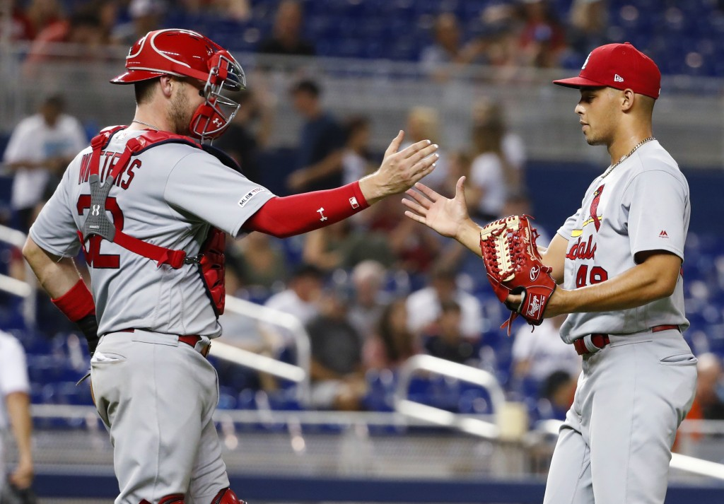 St. Louis Cardinals relief pitcher Jordan Hicks, right, and catcher Matt Wieters congratulate each other after they defeated the Miami Marlins in a ba...