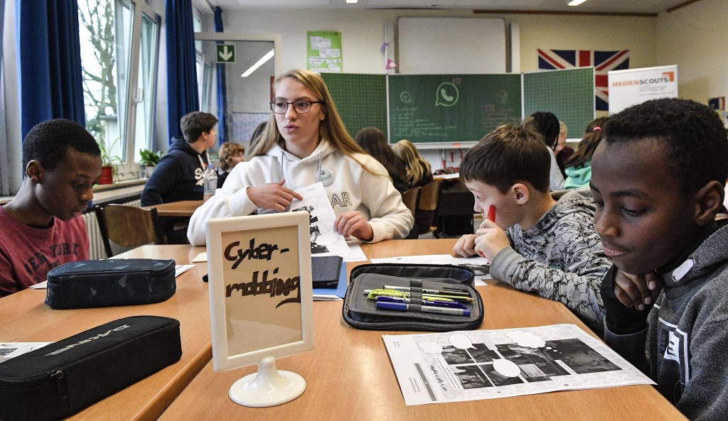 Senior student and media scout Joeline Klaar teaches young pupils behind a sign reading 'Cyber Mobbing' during a lesson in social media and internet a...