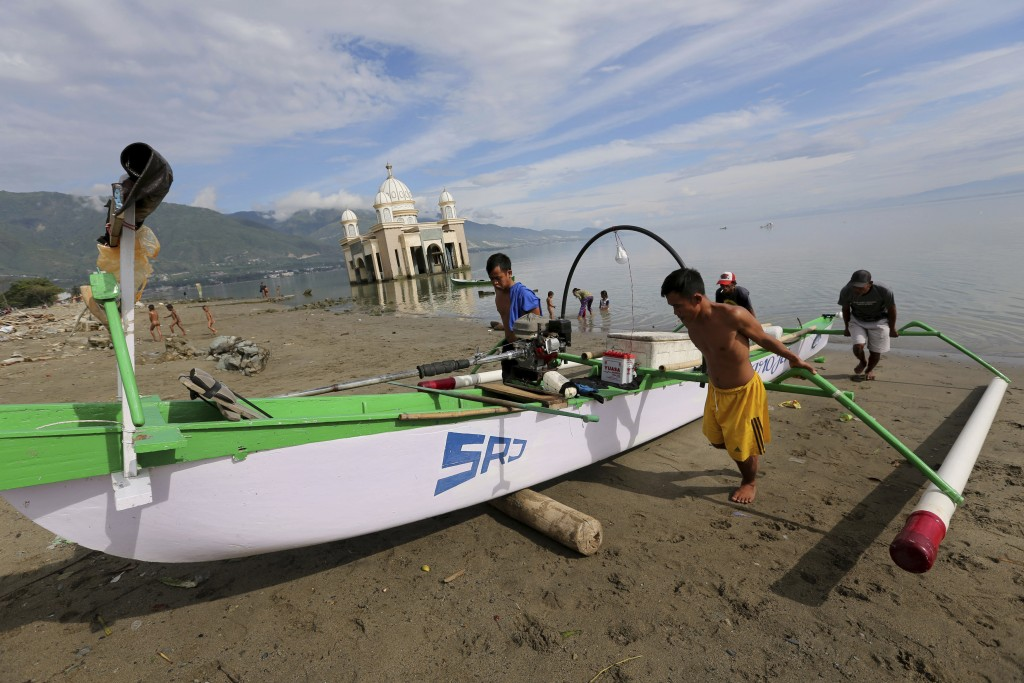 In this April 3, 2019, photo, local fishermen pull a boat to the beach as a mosque heavily damaged by the 2018 earthquake and tsunami is seen in the b