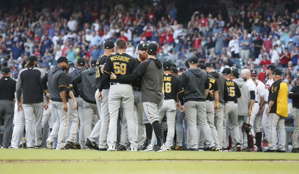 Pittsburgh Pirates starting pitcher Joe Musgrove (59) is held back by his teammates during a brief scuffle with the Atlanta Braves in the first inning