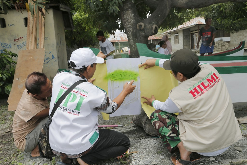 In this April 2, 2019, photo, members of Islamic Defenders Front paint their group's logo as they help local fishermen to build boats at a fishing vil