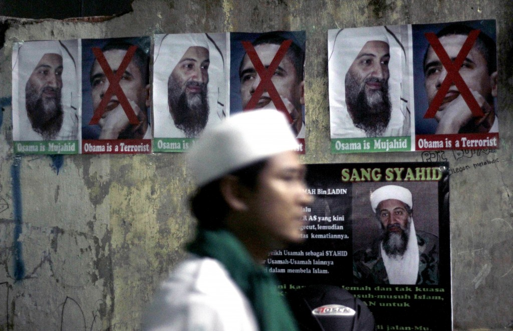FILE - In this May 4, 2011, file photo, a member of radical group Islam Defenders Front walks past posters of Osama Bin laden and U.S. President Barac